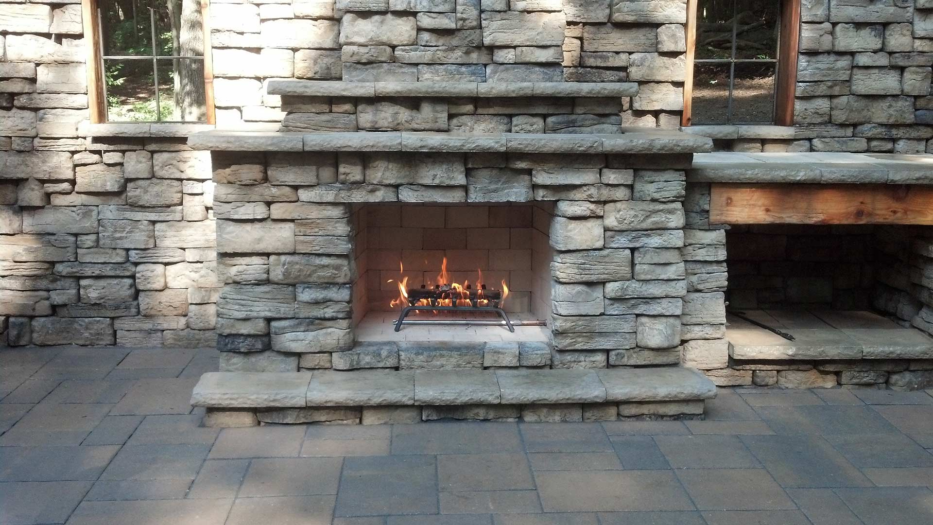 Custom stone outdoor fireplace on a home property in Spring Lake, MI.