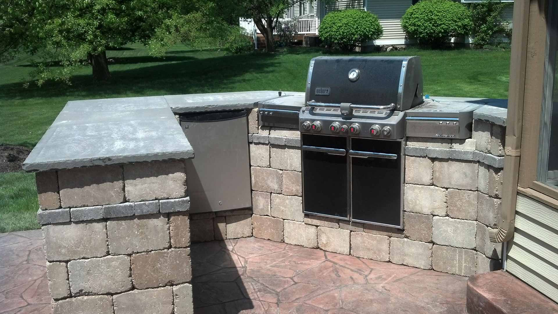 Custom outdoor kitchen installation with a grill in Wyoming, MI.