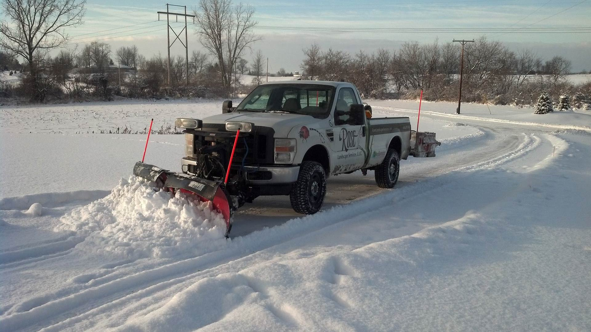 Rose Landscaping company truck plowing snow in Grand Rapids, MI.