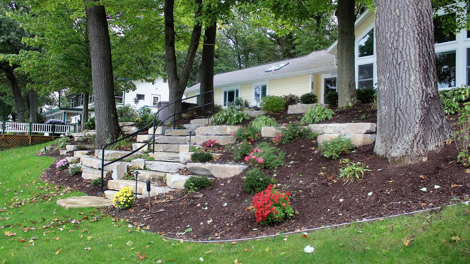 Large mulch flower bed and stone landscaping design in Ada, MI.