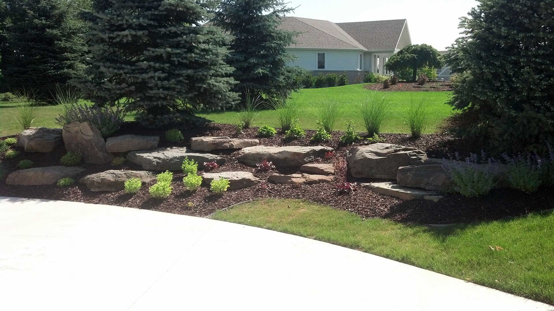 Custom landscaping plant bed at residential property in Grand Rapids, MI.