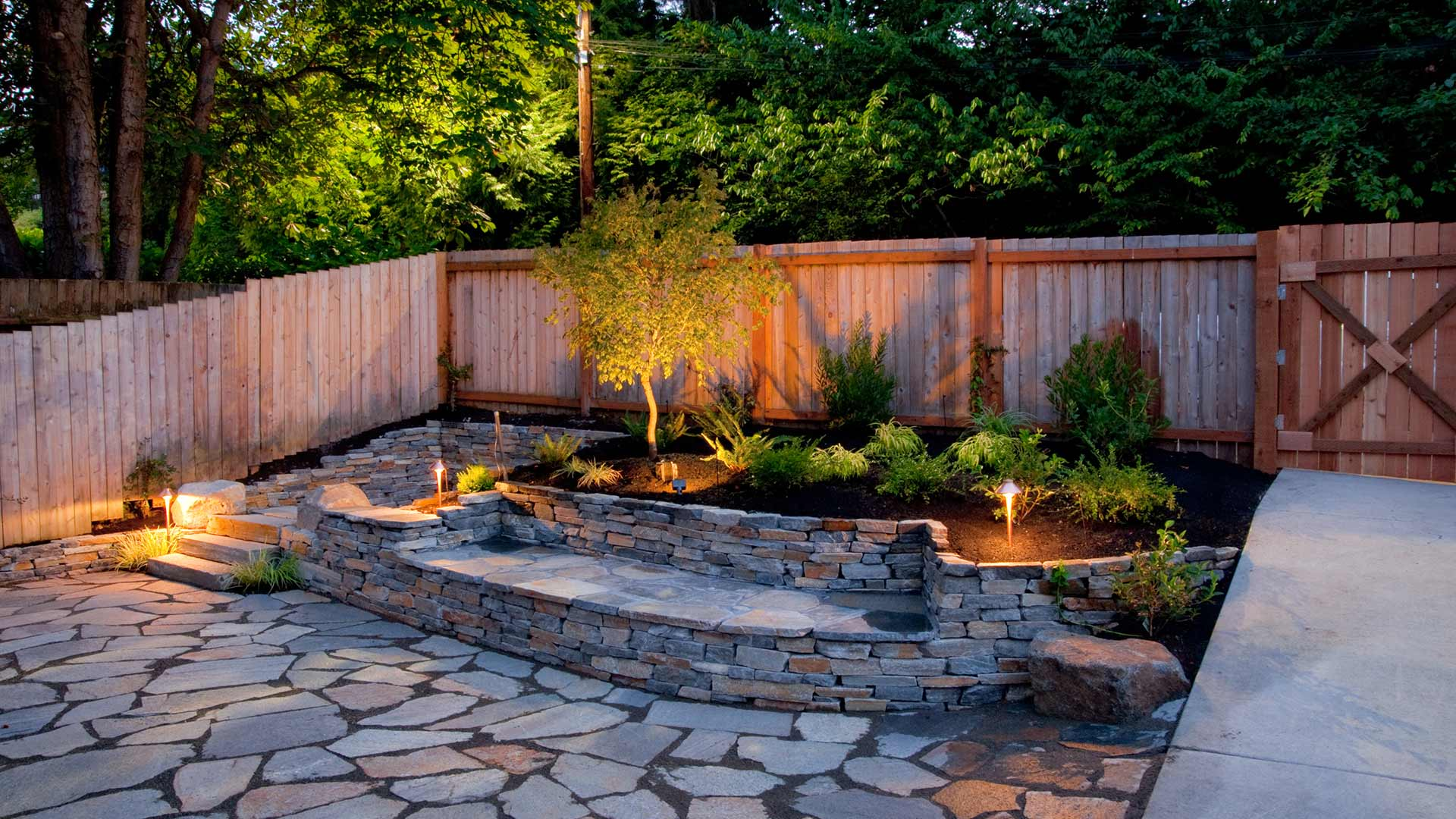 Custom stone patio with retaining wall and outdoor lighting in Cascade, MI.