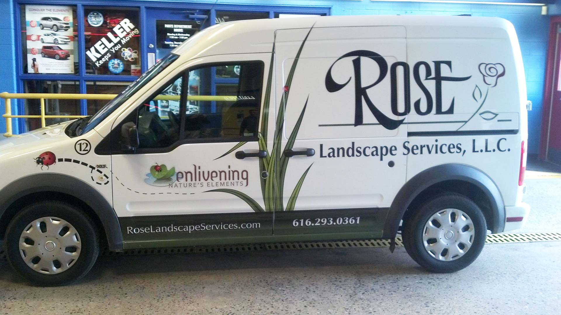 Landscaping company work van with logo and phone number.