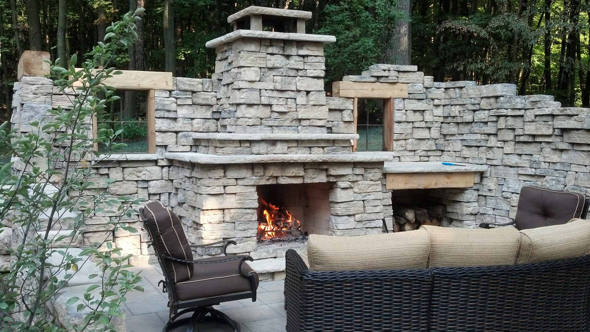 Custom stone outdoor fireplace and seating area in Grand Rapids, MI.