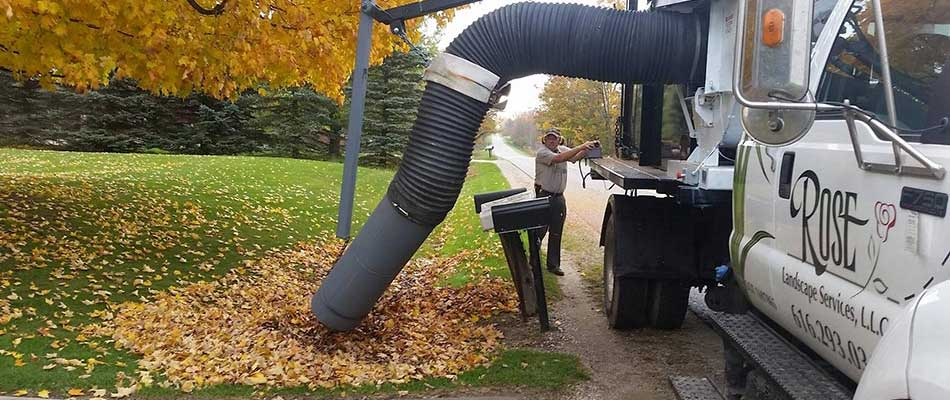 A Rose Landscape Services work truck removing leaves from a Ada, MI property.
