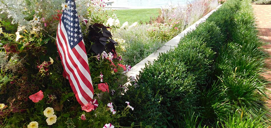 American flag and softscape plantings near a Ada, MI home.