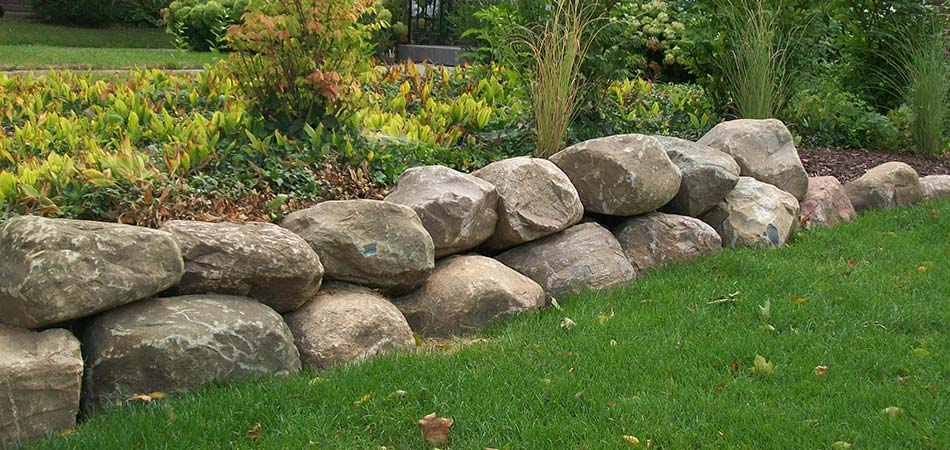 Custom boulder retaining wall and flower bed in Cascade, MI.