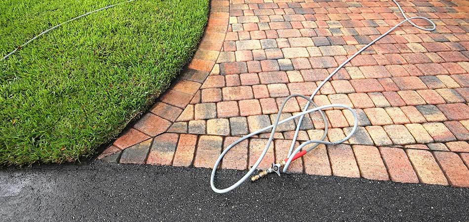 Red brick decorative driveway pressure washed in Ada, MI.