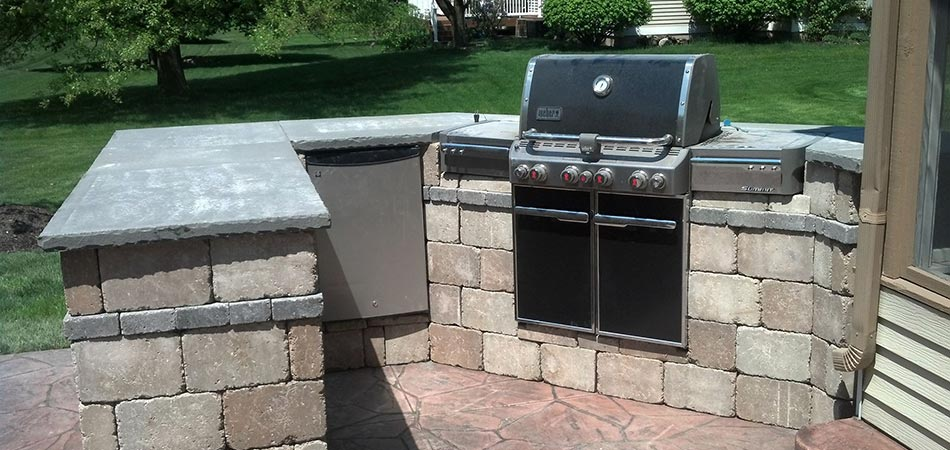 Outdoor kitchen cooking area with gas grill and stone countertop in Cascade, MI.