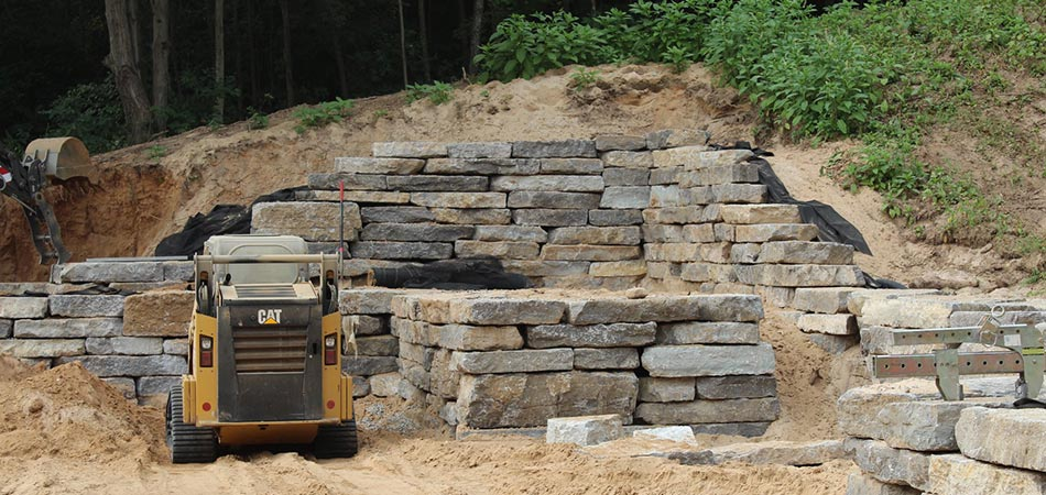 Custom stone retaining wall and outdoor living area being constructed in Cascade, MI.