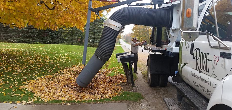 Rose Landscape Services work truck removing leaves from a Grand Rapids, MI lawn.